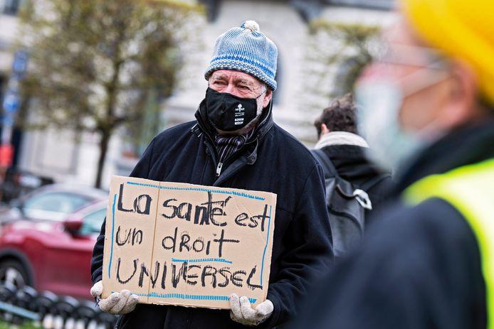 """Een man protesteert in Brussel voor het opheffen van de patenten op coronavaccins en -behandelingen. """"Gezondheid is een mensenrecht"""", staat op zijn bordje te lezen."""