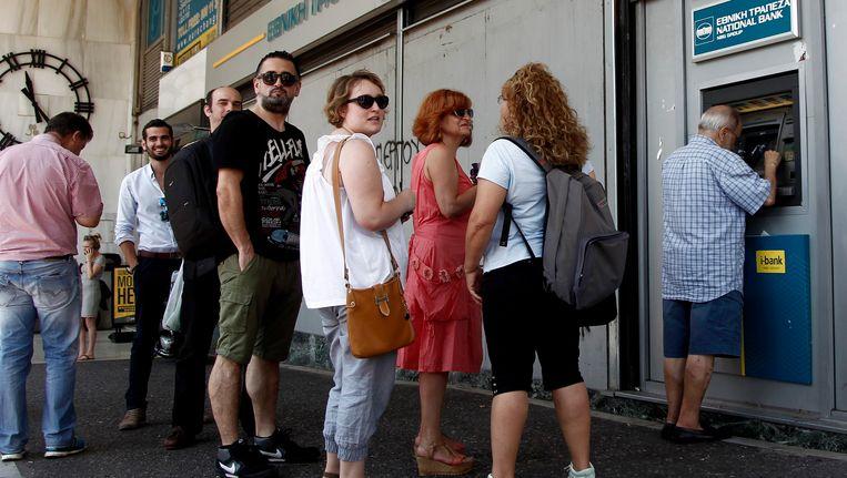Mensen schuiven aan bij een bankautomaat in Athene. Beeld EPA