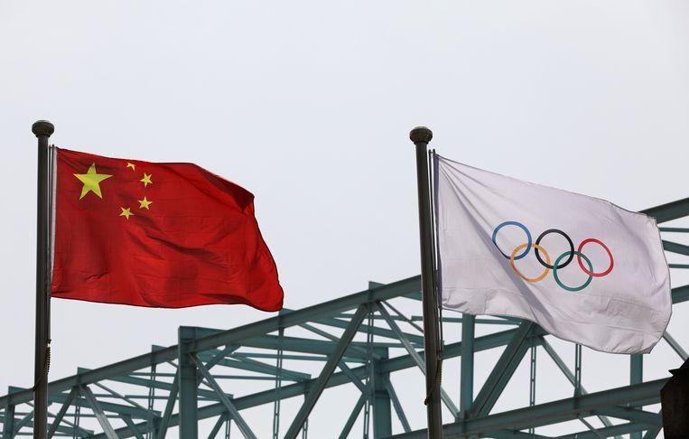 Een Chinese vlag wappert naast de olympische vlag in Peking, waar volgend jaar de Winterspelen en Paralympische Winterspelen worden gehouden. Beeld Reuters