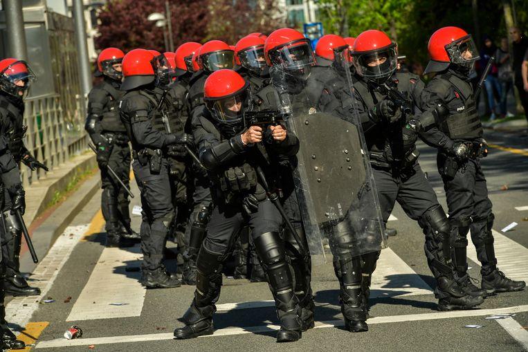 De Baskische anti-oproerpolitie treedt op tijdens betogingen tegen de bijeenkomst van de extreemrechtse partij Vox in Bilbao. Beeld AP