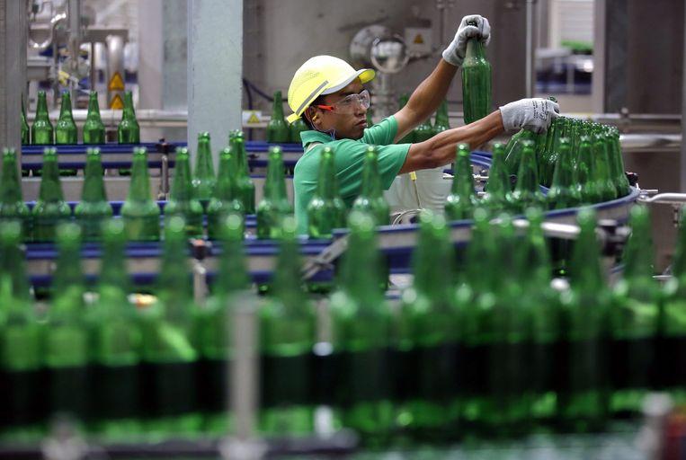 Een medewerker in de fabriek van Heineken in Myanmar. Beeld EPA