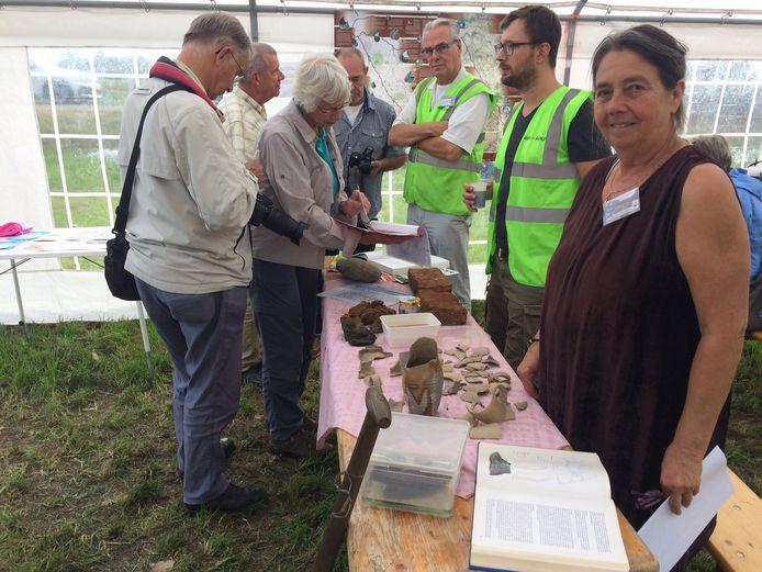 Hanneke van Alphen van de Udense werkgroep archeologie toont de vondsten die bij toeval uit de sleuf tevoorschijn zijn gekomen.