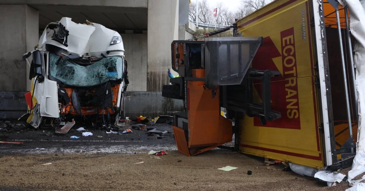 Vrachtwagen uiteengerukt bij botsing tegen brugpijler, chauffeur loopt zwaar hoofdletsel op.