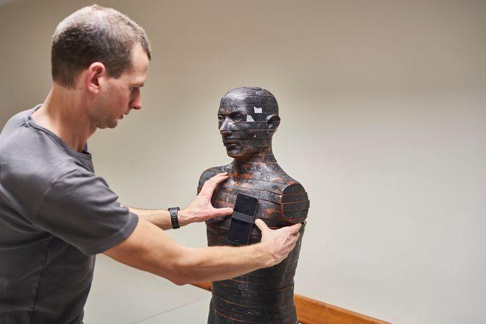 Onderzoeker van het nucleaire onderzoekscentrum SCK CEN bevestigt een smartphone op een anatomische torso voor het meten van blootstelling aan straling.