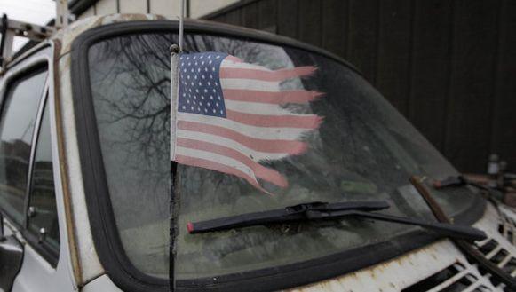 Een gerafelde Amerikaanse vlag wappert aan de auto voor het huis van Thomas W. Piatek, een van de verdachten.