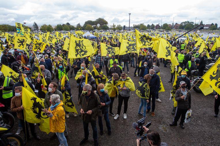 Demonstranten met Vlaamse Vlaggen en mondmaskers die de Vivaldi-coalitie die in de steigers staat niet zien zitten. Beeld BELGA