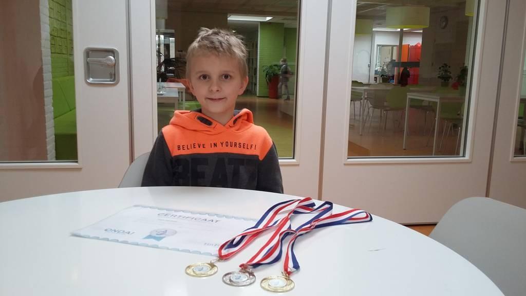 Floris met medailles en certificaat op zijn school De Overlaat in Tolkamer. Foto DG