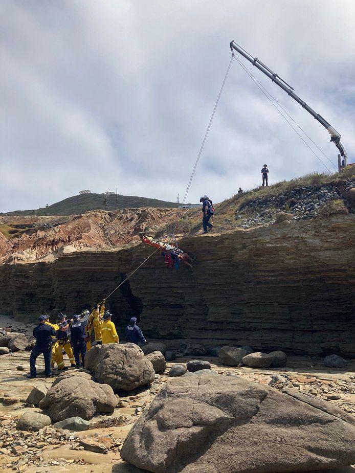 De hulpdiensten repatriëren een gewond slachtoffer van de gekapseisde boot.