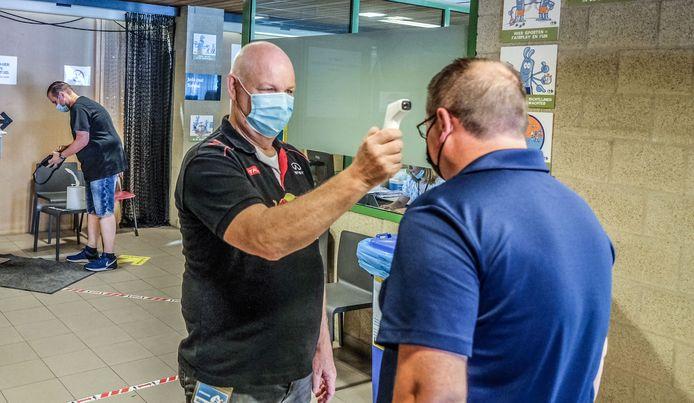 Vrijwilliger Brian Claeys neemt de temperatuur op van de mensen die binnenkomen.