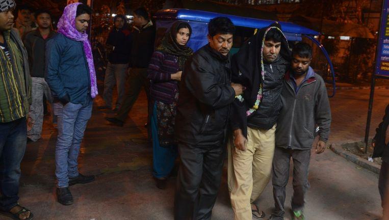 Een gewonde inwoner van de Indiase stad Siliguri wordt naar het ziekenhuis gebracht. Beeld afp