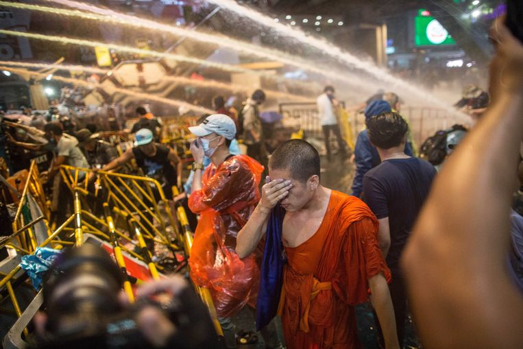 Een monnik veegt de pepperspray van zijn gezicht tijdens een presentatie in Bangkok.  Beeld Photo News
