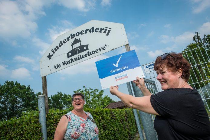 Voorzitter Nellie de Graaf (links) samen met Annemieke Mennega, die trots het nieuwe bord 'rookvrij' toont. Morgen is de officiële onthulling.