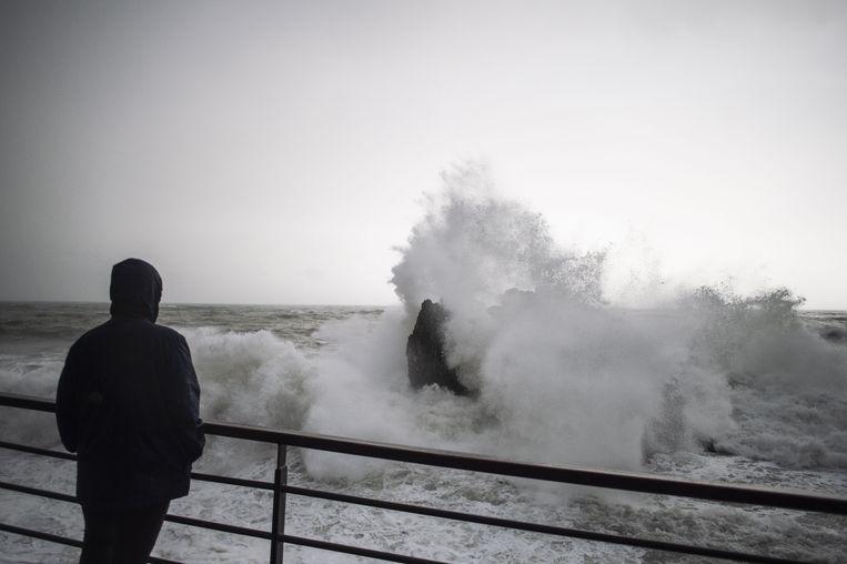 Een man kijkt naar de woeste golven in  Monterosso in de Italiaanse regio Ligurië. Beeld AFP
