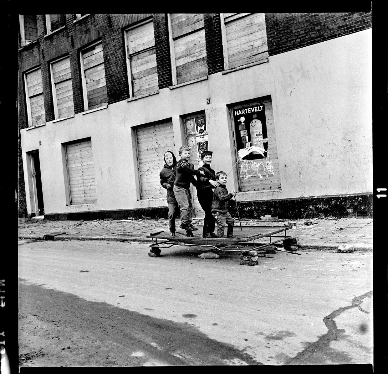 Kattenburg, november 1966. Derde Kattenburgerdwarsstraat. Vier jongens springen op een zelfgemaakte trampoline. Een beddenspiraal op stenen.  Beeld bert verhoeff