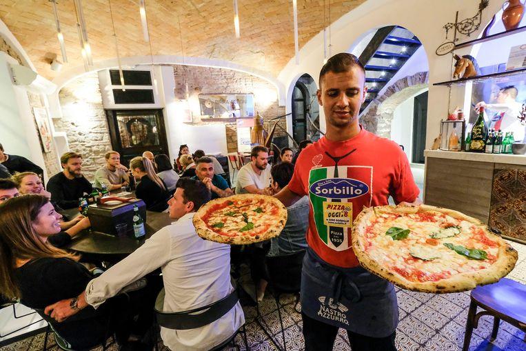 Een ober serveert twee pizza's in een restaurant in Napoli.  Beeld null