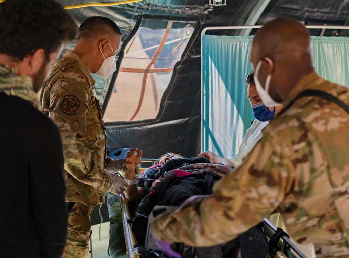 Soldaten omringen de pas bevallen vrouw na de landing op de Amerikaanse luchtbasis Ramstein in Duitsland.