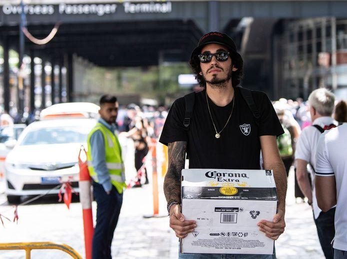 Een man draagt een doos Corona-bier in de buurt van de passagiersterminal in Sydney, waar een Noors cruiseschip ligt aangemeerd.