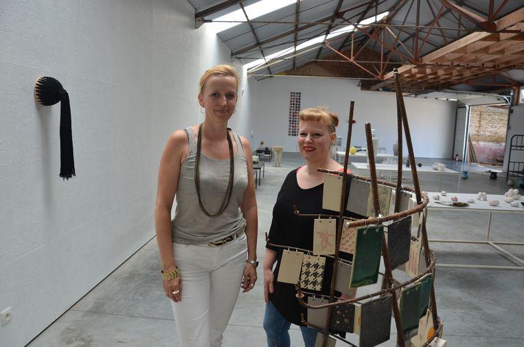 Docenten keramiek Anja Vermeir en An Van den Abbeele bij een van de kunstwerken van hun cursisten.