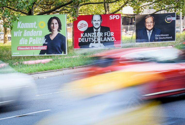 Automobilisten in Berlijn rijden langs de verkiezingsposters van Olaf Scholz (SPD), Armin Laschet (CDU) en Annalena Baerbock (Groenen), de belangrijkste kandidaten om Angela Merkel op te volgen als Bondskanselier van Duitsland. Beeld Kay Nietfeld/dpa