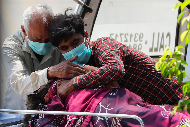 Familie rouwt bij het lichaam van een vrouw die voor de deur van het Lok Nayak Jai Prakash Narayan ziekenhuis in New Delhi is overleden.  Beeld Reuters