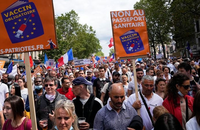 Protestors hold up signs that read 'no to the vaccine passport' during a demonstration in Paris, France, Saturday, July 31, 2021. Demonstrators gathered in several cities in France on Saturday to protest against the COVID-19 pass, which grants vaccinated individuals greater ease of access to venues. (AP Photo/Michel Euler)