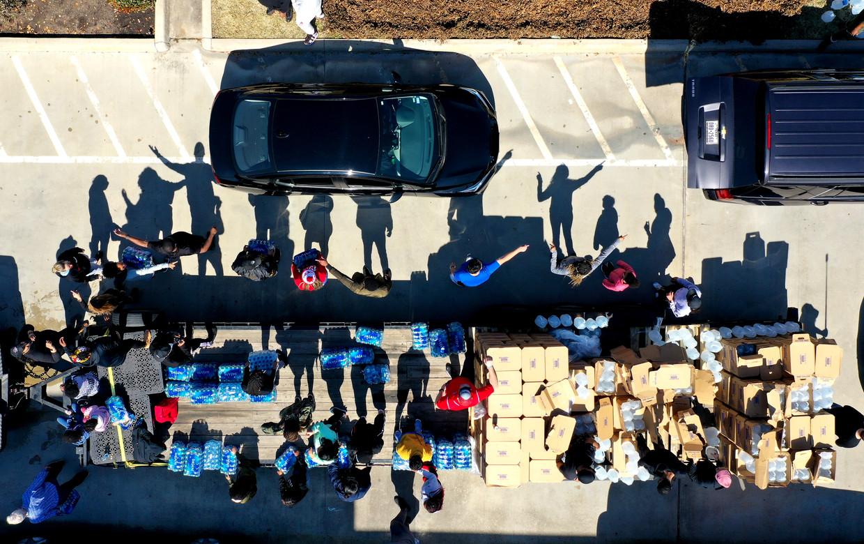 Vrijwilligers delen zaterdag water en voedsel uit in Houston. De temperatuur is na de extreme kou opgelopen tot 20 graden. Beeld Getty