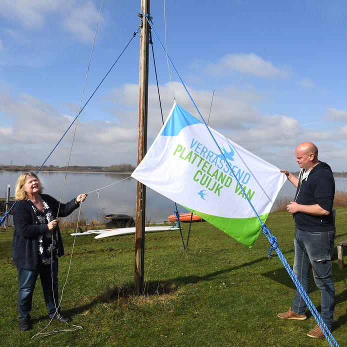 Jaap Ceulemans en Jenneke van Dongen hijsen de vlag met het nieuwe logo van Verrassend PlatteLand van Cuijk.