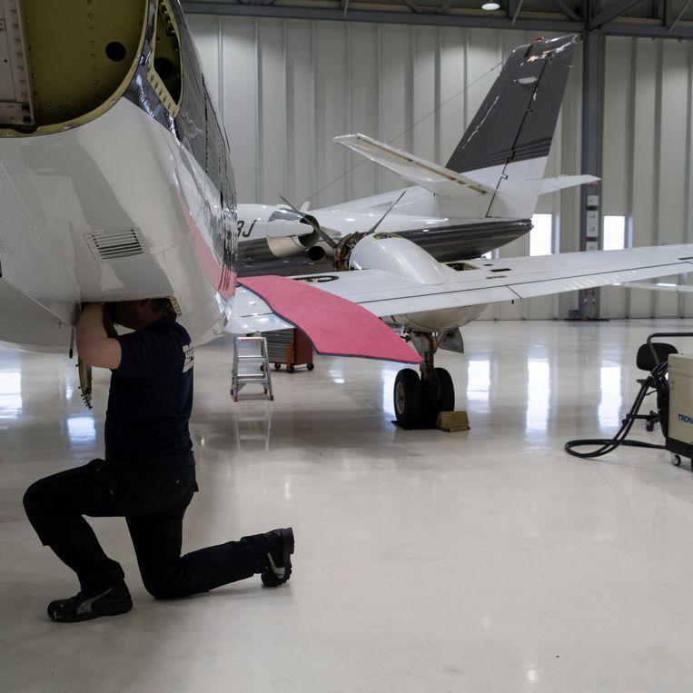 Een monteur controleert een privéjet in een loods op Rotterdam Airport. Beeld Sabine van Wechem