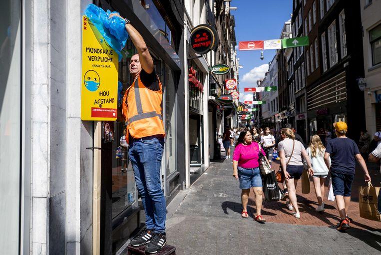 Een bord met informatie over mondkapjesplicht wordt onthuld op de Nieuwendijk.  Beeld ANP