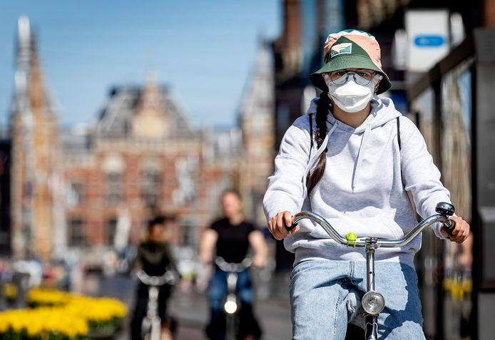 Een fietser in Amsterdam draagt een mondkapje.