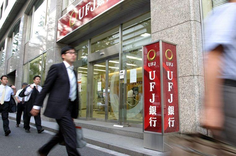 Een Japanse zakenman loopt langs de Japanse UFJ bank. Beeld epa