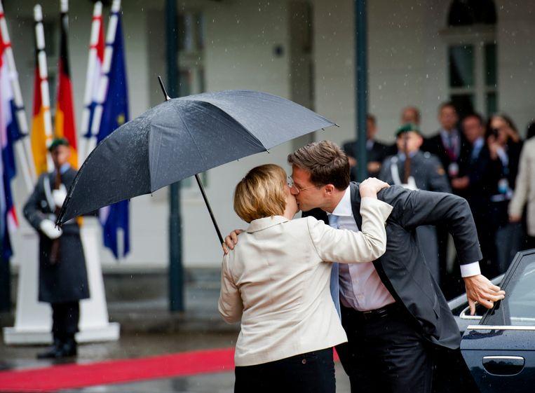 Een beeld uit de tijd voor de coronacrisis: bondskanselier Angela Merkel en premier Mark Rutte begroeten elkaar. Beeld Hollandse Hoogte /  ANP