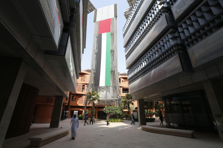 De campus van de duurzame wijk, gebouwen met traditionele elementen. Foto links: de hoge windtunnel die voor verkoeling zorgt Beeld AFP