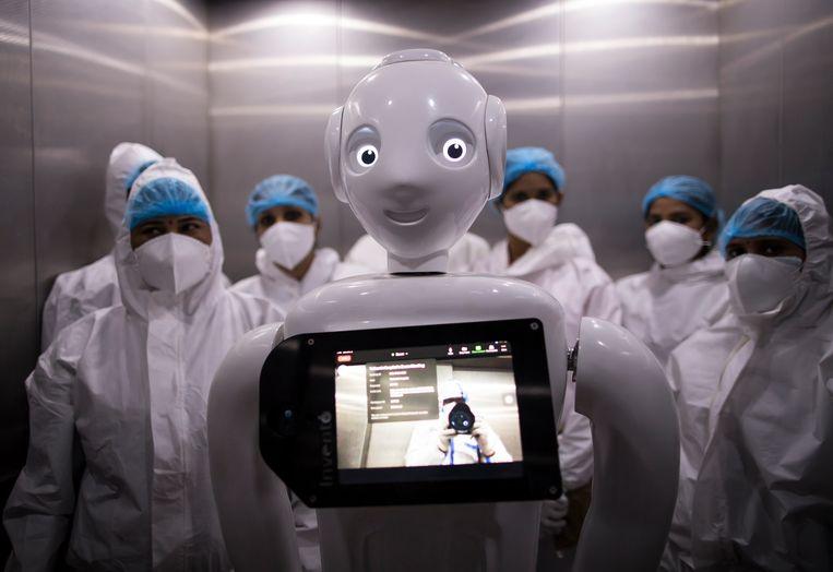 Het grote voordeel van deze robot is in ieder geval dat hij niet besmet kan raken. Deze Mitra helpt in het ziekenhuis van het Indiase New Delhi corona-patiënten bij hun contact met het thuisfront. De monitor in de borst laat de familie zien, terwijl een camera de patiënt voor de familie zichtbaar maakt. Tweede voordeel: Mitra lacht altijd.  Beeld Getty Images
