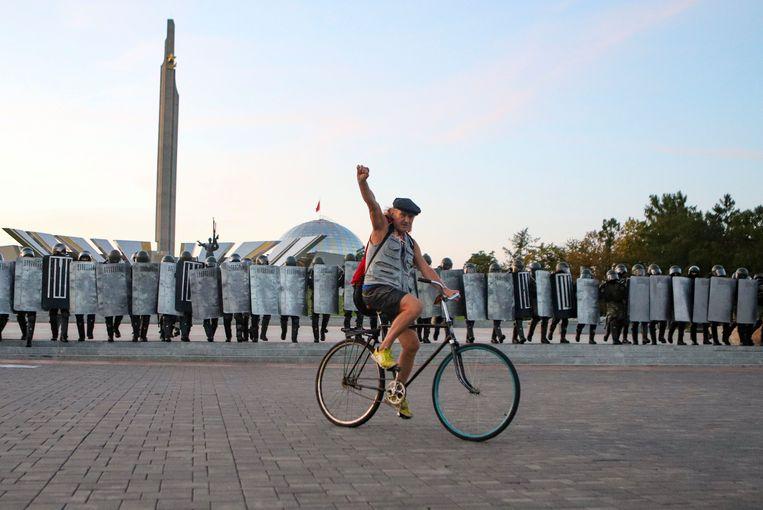 Een demonstrant op de fiets rijdt voor de Belarussische politie langs tijdens een protest in Minsk, Belarus. Beeld AP