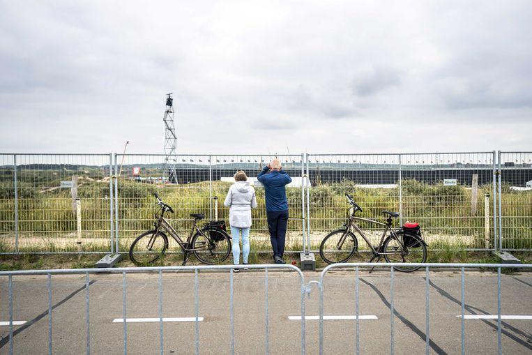 Voorbijgangers proberen een glimp op te vangen van de voorbereidingen van de Formule 1-race op het circuit van Zandvoort. Beeld ANP