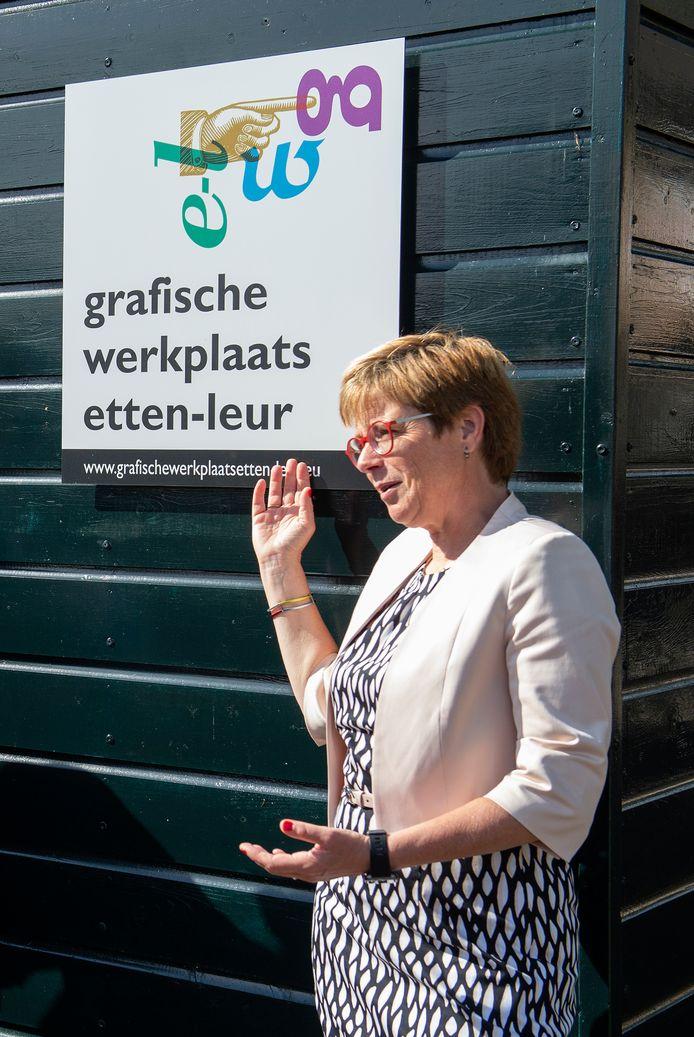 Burgemeester De Vries onthult de plaquette op de gevel van de nieuwe grafische werkplaats van het Drukkerij Museum.