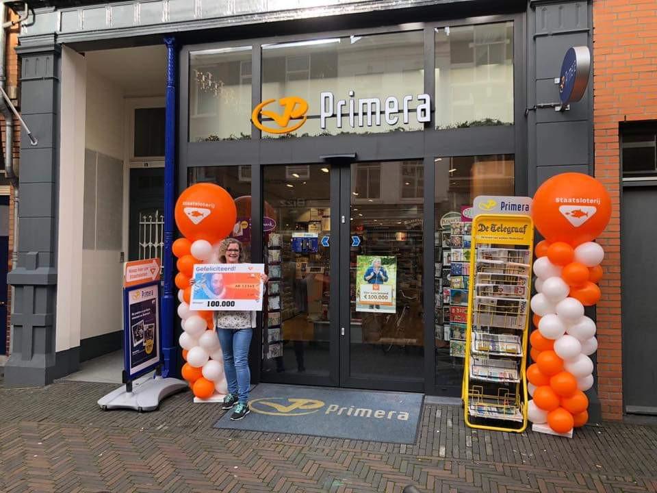 Een medewerkster van de Primera in de Arnhemse Steenstraat Arnhem met een vergroting van het lot waarop een prijs van 100.000 euro is gevallen.