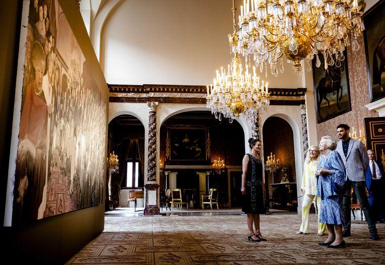 Prinses Beatrix bezoekt kijkt naar het schilderij The Family van Helen Verhoeven. Het is een historisch familieportret van de Oranjes. Beatrix staat er zelf, helemaal links, ook op. Beeld Sem van der Wal / ANP