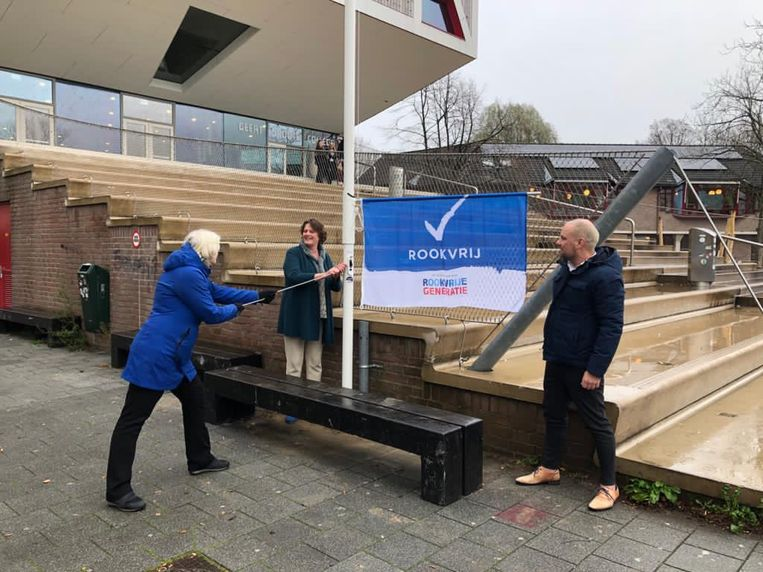 Stadsdeelbestuurder Rocco Piers (r) opent met twee initiatiefnemers voor de ingang van het Geert Grote College de rookvrije straat. Beeld Gemeente Amsterdam