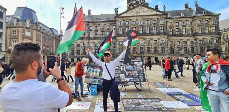 Jongeren maken een foto met Palestijnse vlag op de Dam. Beeld Noël van Bemmel