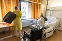 Verpleegkundige Wendy (26) haalt een rolstoel, helpt Mieke in haar jas en pakt haar koffer in.