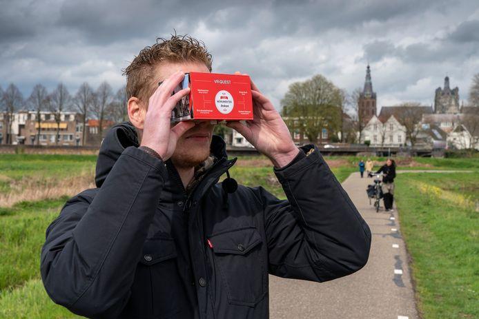 De VR-bril waarmee de vier Brabantse topmonumenten met je mobiele telefoon te zien zijn. Op de achtergrond: de Sint-Jan in Den Bosch.