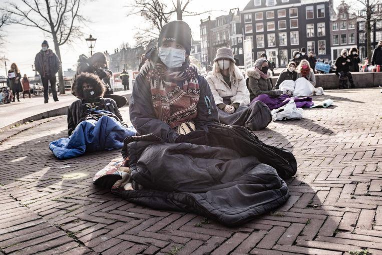 Amsterdam, Nederland, 16/12/20 | Daklozen en sympatisanten demonstreren bij de Stopera, ze liggen in een slaapzak op het plein. Dak- en thuislozen opvang is een structureel en groeiend probleem in Amsterdam. . Foto: Joris van Gennip Beeld Joris Van Gennip