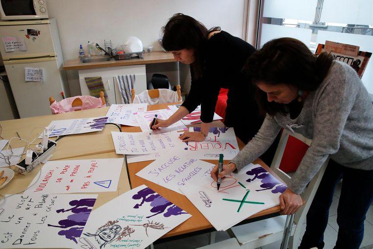 Alix Chazeaux-Guibert (links) en Celinne Piques (rechts) van de feministische organisatie Osez le Feminisme bereiden posters voor. Beeld AP