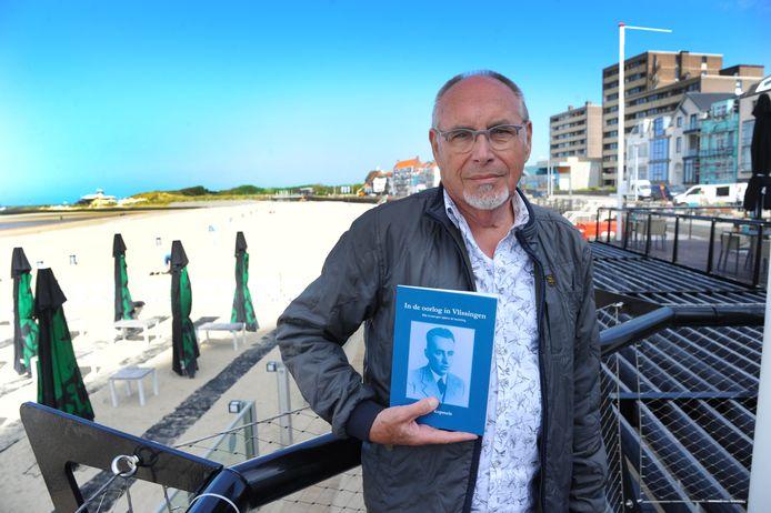 Dook Kopmels met het boekje van en over zijn vader 'In de oorlog in Vlissingen' bij het Badstrand waar zijn vader Duitse verdedigingslinies 'saboteerde'.