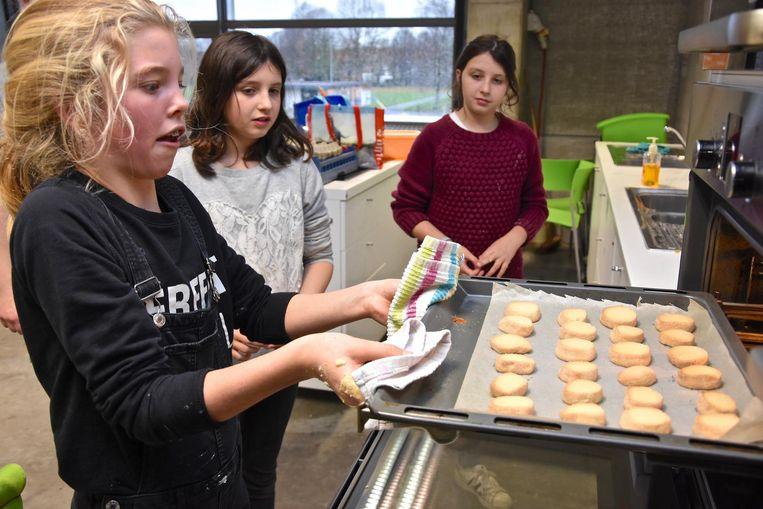 Een leerlinge probeert uiterst geconcentreerd de gebakken koekjes uit de oven te krijgen.