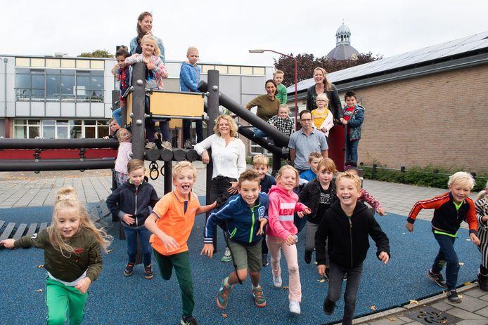 Een deel van het team met kinderen en ouders op de speelplaats. Bovenin het klimrek vlnr leerkrachten Sonja de Winter, Sonja Vissers en directeur Angela Maas. Onderaan Kirsten Aarts (ouderraad) en Jasper Segeren (bestuur).