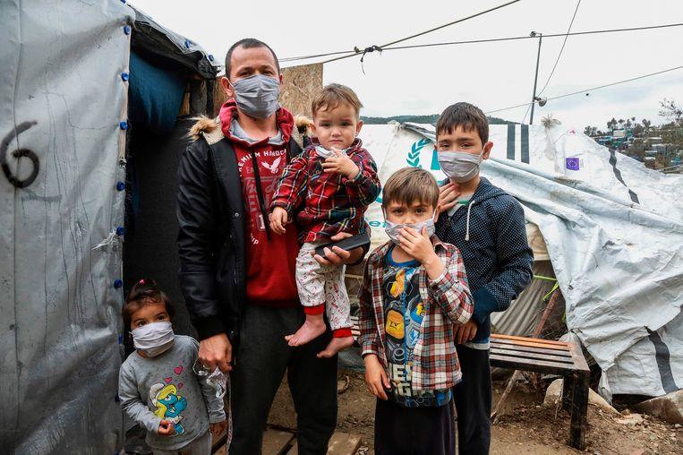 Een migrantenfamilie met mondmaskers in Moria, Lesbos, eind maart 2020.   Beeld AFP