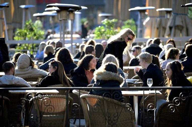 Jongeren op een terras in de Zweedse stad Stockholm. Vooral in Zweedse steden is voor mensen met een laag of gemiddeld inkomen heel lastig om een betaalbare woning te vinden. Beeld Reuters